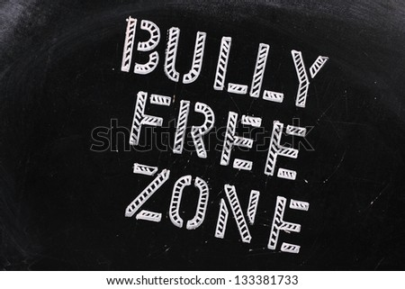 The words Bully Free Zone in chalk stencil letters on a well used blackboard, which might be used for a campaign to stop bullying at school or work - stock photo