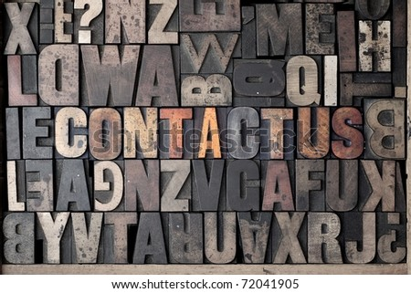 The words 'Contact Us' spelled out in very old letterpress blocks. - stock photo