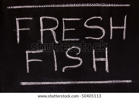The words Fresh Fish written with chalk on a chalk board - stock photo