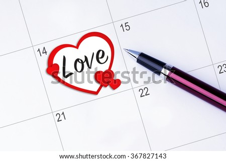 The words Love written on a calendar planner to remind you an important appointment with a pen on isolated white background. Valentine's Day and Love Concepts - stock photo