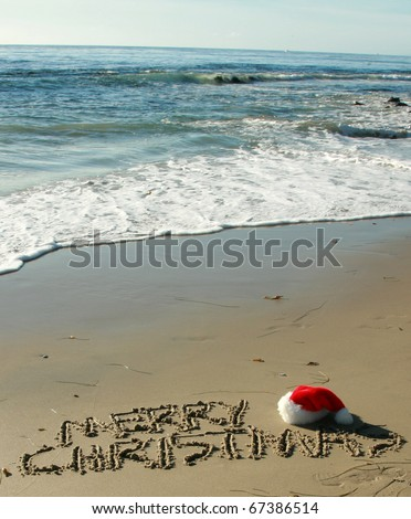 """The words """"Merry Christmas"""" written in the wet sand on a Southern California Beach with a """"Santa Hat"""" and the """"Pacific Ocean"""" in the background - stock photo"""