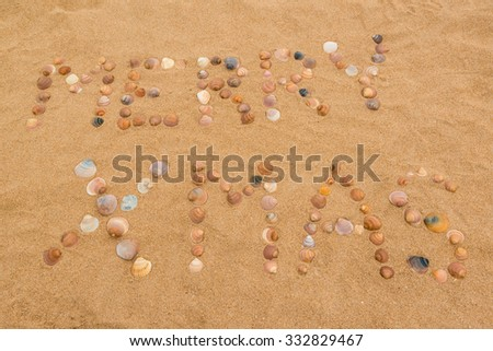 The words Merry Xmas written in the sand on the beach using seashells - stock photo
