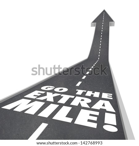 The words or saying Go the Extra Mile on a road with arrow going upward to illustrate improvement, increase and additional effort to accomplish a goal or mission - stock photo
