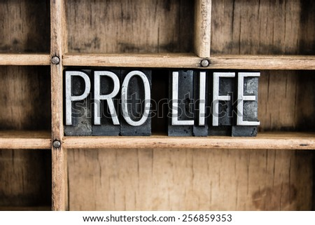 "The words ""PRO LIFE"" written in vintage metal letterpress type in a wooden drawer with dividers. - stock photo"
