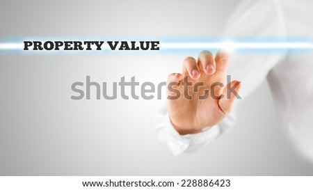 The words - Property value - on a virtual interface contained in a narrow navigation bar with a man activating it from behind with his finger. - stock photo