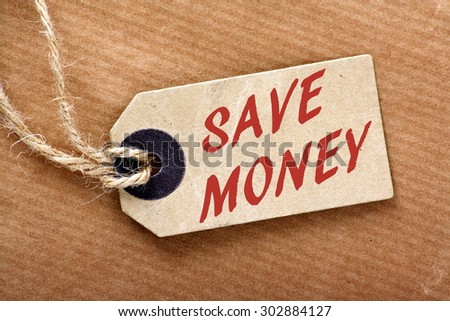 The words Save Money in red text on a price tag or label with string and brown wrapping paper - stock photo