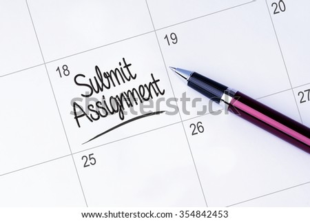 The words Submit Assignment on a calendar planner to remind you an important appointment with a pen on isolated white background.  - stock photo