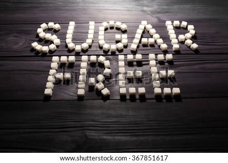 The words 'sugar free', built from white cubes pieces of sugar on background  of panel from vintage wooden boards black color in high contrast dramatic lighting  'Hard light'. Selective focus - stock photo