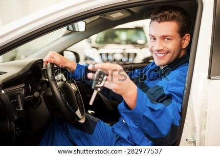 The work is done. Cheerful young man in uniform stretching out hand with keys while sitting in a car at workshop - stock photo
