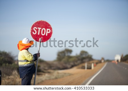 The worker hold the red stop sign at the road in west Australia during road maintenance - stock photo