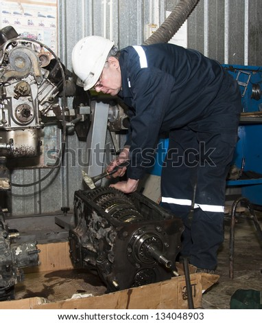 the worker in garage repairs transmission - stock photo