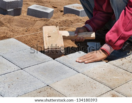 The worker is paving a stone path with wooden hammer - stock photo