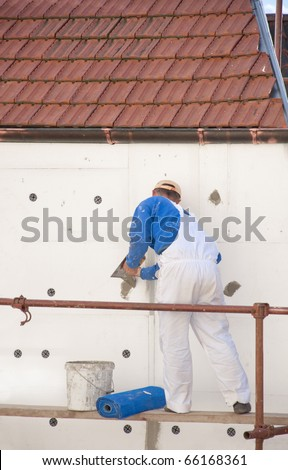 The worker placed the insulation on the building - stock photo