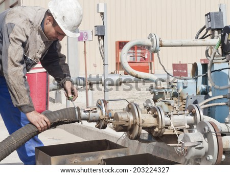 The worker prepares the device for pumping of gasoline - stock photo