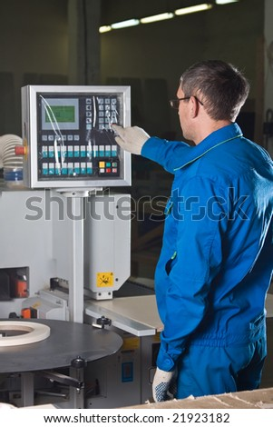 The worker presses buttons of the panel of the machine tool with numerical programmed control - stock photo