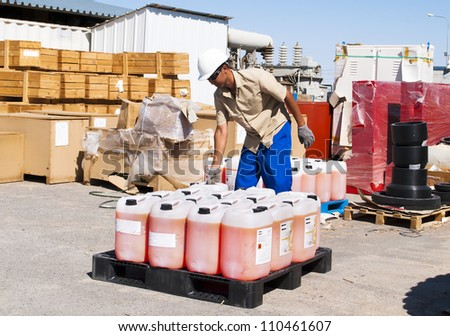 the worker works at a warehouse. Moving of canisters. - stock photo