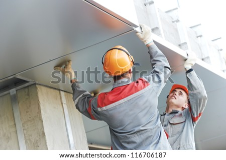The Workers builders doing facade works with metal sheet boarding - stock photo