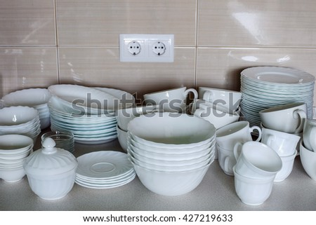 The working zone of a kitchen table-top crammed the mountain of ware: plates and cups. - stock photo