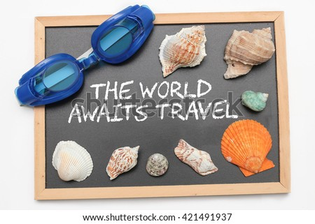 The world awaits travel text on chalk board with swimming goggle and shell - vacation and business concept - stock photo