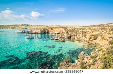 The world famous Blue Lagoon in Comino island - Mediterranean nature wonder in the beautiful Malta - Unrecognizable international tourist people and snorkeling divers - Exclusive travel destinations - stock photo
