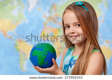 The world in my hands - little girl in geography class holding earth globe, copy space - stock photo