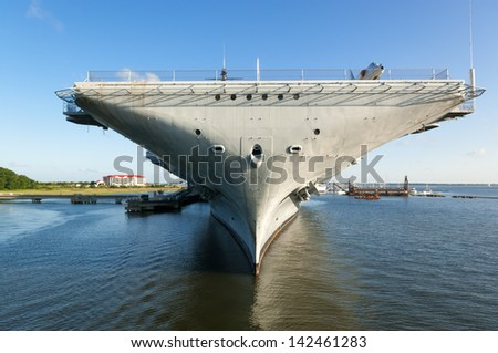 The World War II era aircraft carrier USS Yorktown, docked in the Charleston, SC Harbor with dramatic blue skies and reflections in the water - stock photo