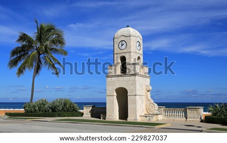 The Worth Avenue Clock Tower on Palm Beach, on the Old Ocean Boulevard, and entrance to the beach and Atlantic Ocean - stock photo