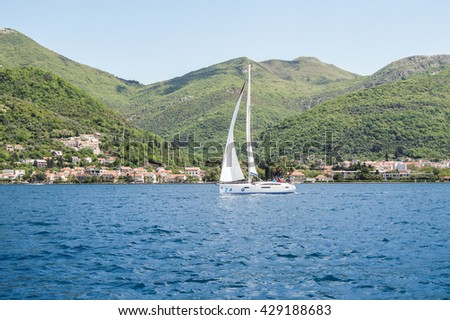 """The yacht on a background of green mountains. Tivat, Montenegro - 26 April, 2016. Regatta """"Russian stream"""" in God-Katorskaya bay of the Adriatic Sea off the coast of Montenegro. - stock photo"""
