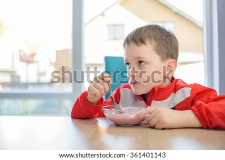 The 6 years old boy eating fruit yoghurt in a bowl. Dressed in a red sweatshirt sitting at a table at home - stock photo