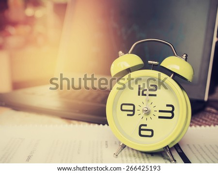 The yellow alarm clock is showing 12 o'clock standing on business documents with finance graph background in vintage style. - stock photo