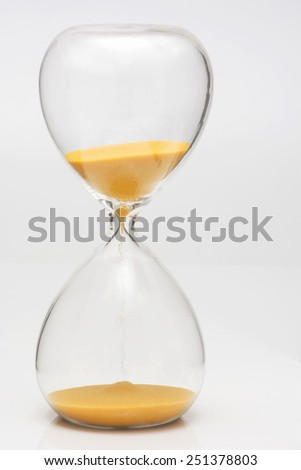 The yellow hourglass on the white background - stock photo