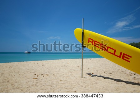 The yellow surf rescue board ready on the beach for accident prevention and water rescue on Nai Harn beach in Phuket thailand - stock photo