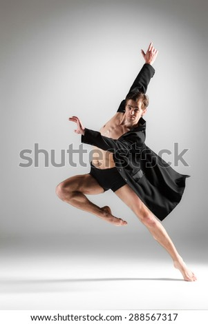 The young attractive modern ballet dancer in black jacket over white background.  - stock photo