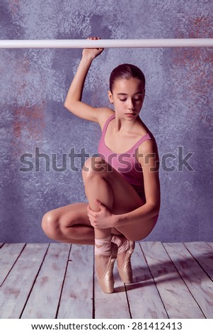 The young ballerina stretching on the bar on lilac background of wooden floor - stock photo