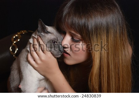 The young beautiful girl holds in hands of a Siamese cat - stock photo
