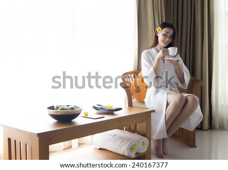 The young beautiful woman has coffee sitting at a window - stock photo