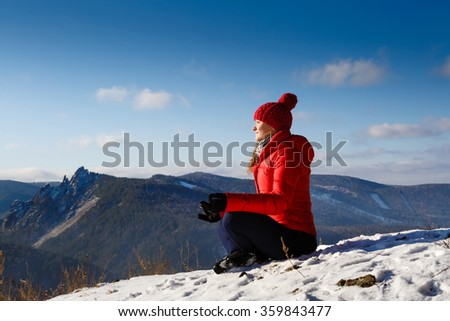 The young beautiful woman in mountains has a rest in the winter at the weekend, soft focus - stock photo