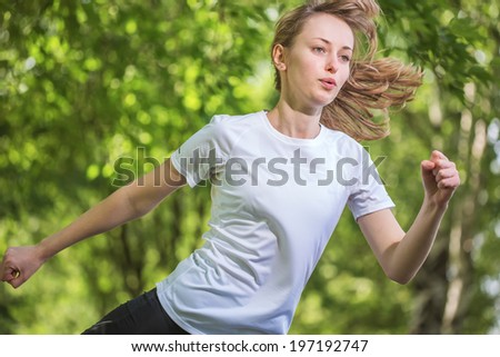 The young beautiful woman runs on park - stock photo