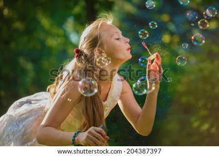 The young blonde blows soap bubbles - stock photo