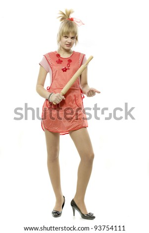 The young blonde in an apron costs the kitchen tool - stock photo