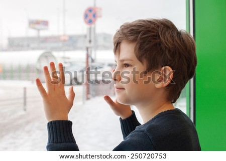 The young boy snuggles against big window in winter day - stock photo