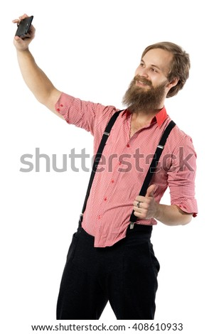 the young brutal man with a beard of the European appearance takes a selfie on a white background in a red shirt with braces and black trousers - stock photo