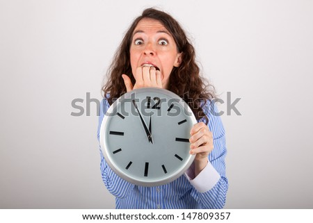 The young business woman is holding a big watch in her hands - stock photo