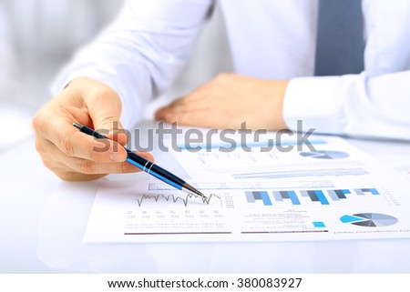 The young businessman showing graphs by pen - stock photo