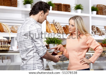 The young couple argues at a shop show-window - stock photo
