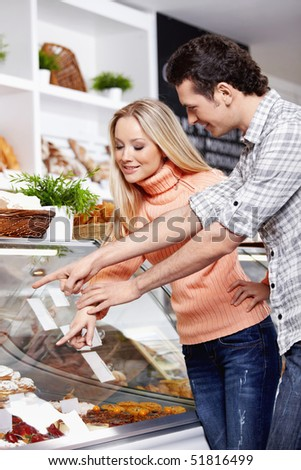 The young couple chooses meal at a shop show-window - stock photo