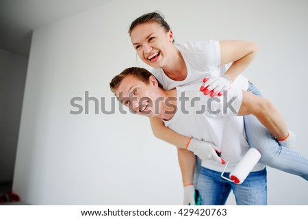 The young couple has fun doing repair in the apartment. The girl has got on a back to the guy. On faces cheerful smiles. Young people hold rollers for paint. Their hands in working gloves. - stock photo