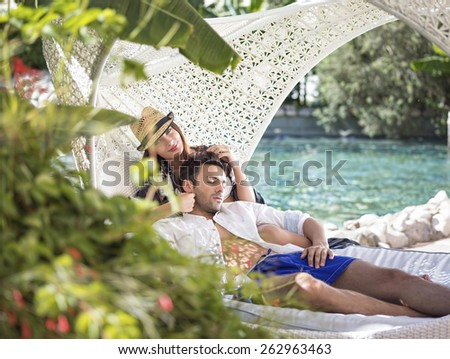 The young couple lying on outdoor sofa - stock photo