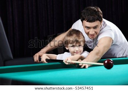 The young father learns the son to play billiards - stock photo