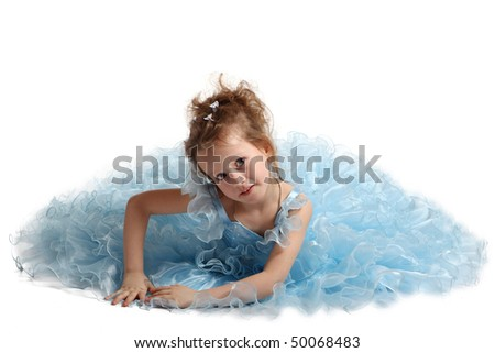 The young fine girl (child) in a blue dress sits on a white background - stock photo